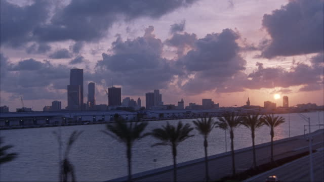 vídeos de stock, filmes e b-roll de aerial along coastal waterway and jetty with setting sun in background. sky at right is orange and buildings are silhouetted against sun. pov moves over water and into downtown area with miami skyline. see sun reflect off of one office building. beautiful - 1995