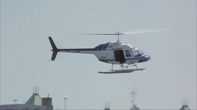 tracking shot of white and blue helicopter flying through air from side to side. tops of buildings in background, see parking structure at bottom at end. - hubschrauber stock-videos und b-roll-filmmaterial