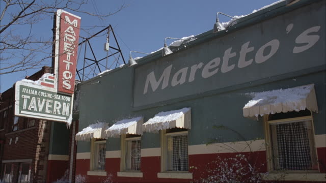 "UP ANGLE OF RESTAURANT. SIGNS READS ""MARETTO'S"" AND ""ITALIAN CUISINE SEA FOOD TAVERN."" SNOW, PROBABLY WINTER. NEG CUT."