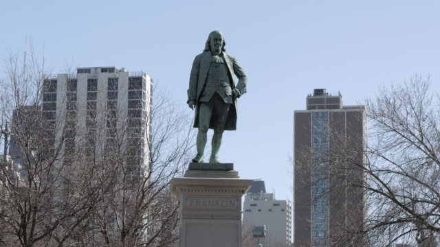 stockvideo's en b-roll-footage met medium angle of statue or monument of benjamin franklin. trees visible in fg. high rise office or apartment buildings visible in bg. could be lincoln park. - monument