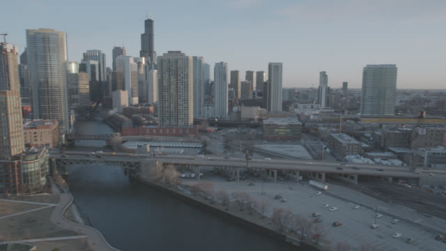 wide angle of chicago city skyline with bridges, chicago rivers, and high rises office buildings. skyscrapers and landmarks. sears tower visible in bg. parking lots and freeways or highways visible. cars visible driving over bridges. construction cranes i - willis tower stock videos & royalty-free footage