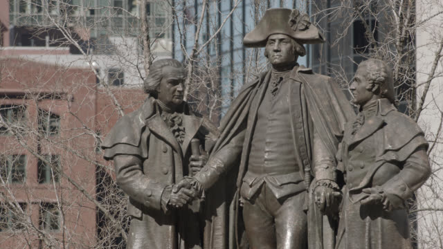 medium angle of statue or sculpture of george washington, robert morris, and haym saloman in chicago. heald square. buildings partially visible in bg. - george washington stock videos and b-roll footage