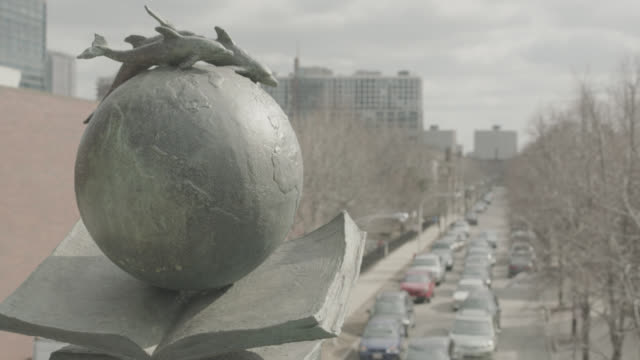 CLOSE ANGLE OF SCULPTURE OF OPENED BOOK WITH GLOBE AND SWIMMING DOLPHINS. BUILDINGS VISIBLE IN BG. CARS VISIBLE DRIVING ON CITY STREET. COULD BE LIBRARY. ACTUAL LOCATION IS ROOSEVELT ROAD BRIDGE.
