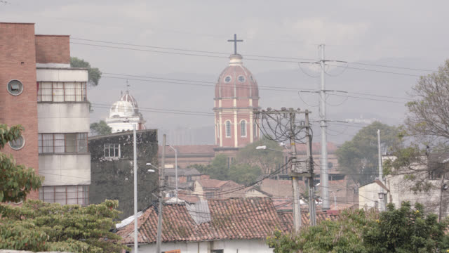 wide angle of city or downtown area in ecuador. domed church with cross steeple visible in bg. trees, spanish style roofs. telephone poles and wires, and multi-story apartment or office buildings visible. - religious equipment stock-videos und b-roll-filmmaterial
