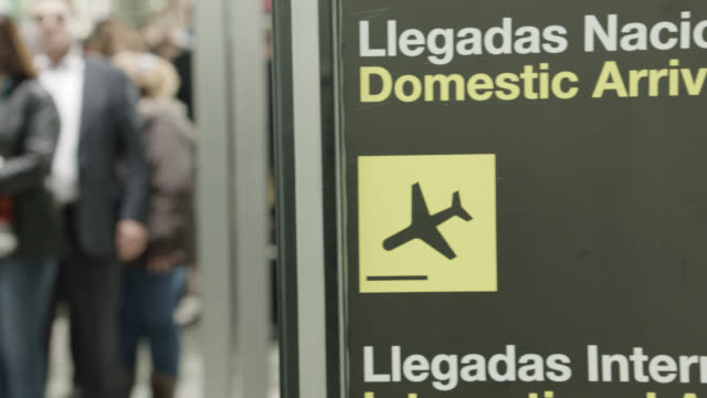 medium angle of people or passengers passing through security line or checkpoint at airport. sign in spanish visible in fg reading 'domestic arrivals.' armed security guards  soldiers visible. luggage. - security staff stock videos & royalty-free footage