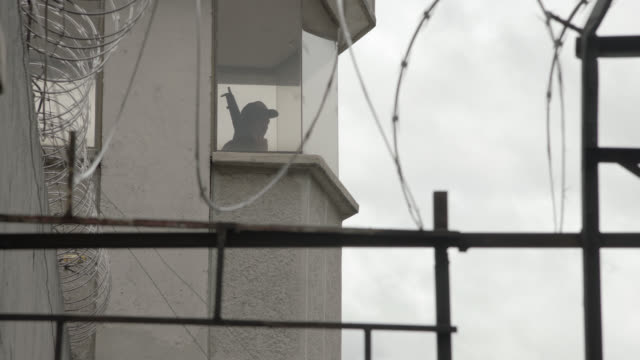 medium angle of guard tower in prison camp area. barbed wire fence visible in fg. could be wall. security guard armed with weapon visible in tower. machine guns. - 武器点の映像素材/bロール