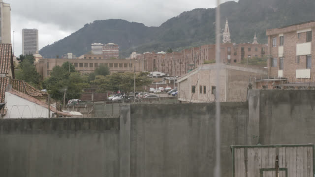 pan up from prison camp area to medium angle of city skyline by mountains. churches, steeples, apartment buildings, and office buildings visible above barbed wire topped wall. could be fence. camera pans back down to prison yard area with basketball hoop, - prison wall stock videos & royalty-free footage