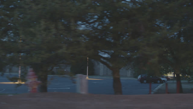 medium angle moving pov of car driving past police station. could be school or hospital. large parking lot in front of building. could be rural or residential area. - georgia country stock videos and b-roll footage