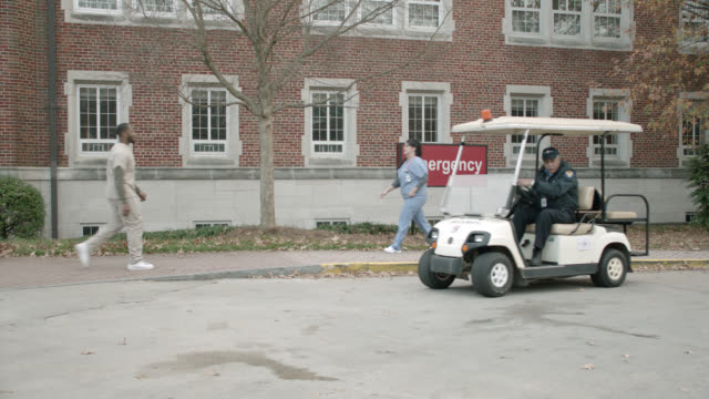 "vídeos de stock, filmes e b-roll de wide angle of brick building with sign reading ""emergency."" could be hospital or medical center. nurse in scrubs takes ride from security guard in golf cart. staff visible. - golf cart"