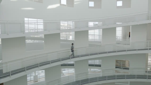 wide angle of multi-story building with circular ramps or hallways snaking upwards. could be hospital or medical center. window visible. could be art museum. security guard in uniform walks up ramp and then back down again. - guardia di sicurezza video stock e b–roll