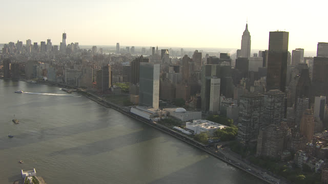 aerial of manhattan new york city skyline. skyscrapers, high rise and multi-story office or apartment buildings. east river. united nations building. midtown manhattan. glass building. - east river stock videos & royalty-free footage