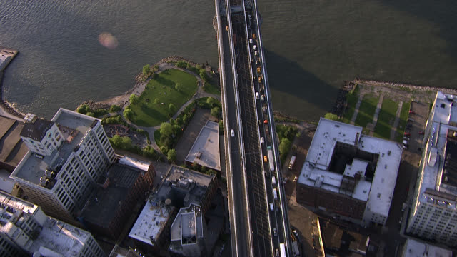 aerial bird's eye pov over manhattan bridge to manhattan, the bowery, soho and west village. downtown manhattan city skyline and brooklyn bridge. skyscrapers and high rise and multi-story office or apartment buildings. traffic. - brooklyn bridge bildbanksvideor och videomaterial från bakom kulisserna