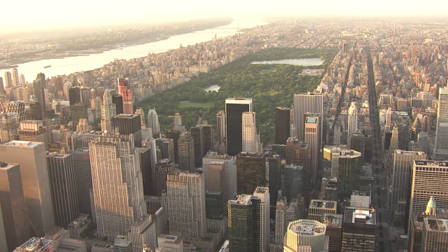 aerial of new york city skyline, midtown manhattan. empire state building. skyscrapers and high rise office or apartment buildings. central park. hudson river in bg. sunset. - river hudson stock videos & royalty-free footage