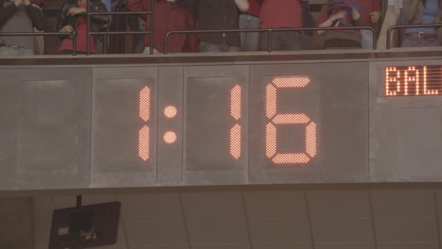 stockvideo's en b-roll-footage met wide angle of digital scoreboard timer counting down from one minute 40 seconds to zero. fans or spectators cheering and clapping above digital display. could be sporting event. sports. - 40 seconds or greater