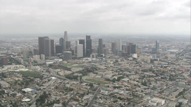 aerial of downtown los angeles skyline. city skylines. high rises, skyscrapers, and office buildings visible. us bank tower. harbor freeway 110 with cars, traffic. highways. athletic fields visible. - us bank tower stock videos & royalty-free footage