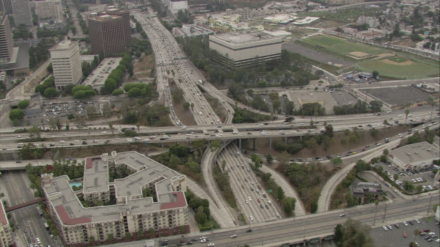 AERIAL OF HARBOR FREEWAY 110 AND HIGHWAY 101 INTERSECTIONS WITH CARS, TRAFFIC. DOWNTOWN LOS ANGELES. OVERPASSES, RAMPS.
