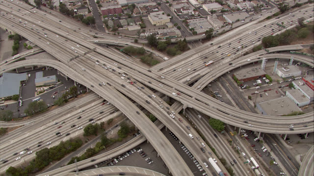 AERIAL OF HARBOR FREEWAY 110 AND HIGHWAY 101 INTERSECTIONS. BIRDSEYE POV OF CARS, TRAFFIC. PAN UP TO REVEAL LOS ANGELES DOWNTOWN SKYLINE, CONVENTION CENTER. HIGH RISES, SKYSCRAPERS, HOTELS, OFFICE BUILDINGS. OVERPASSES, RAMPS.