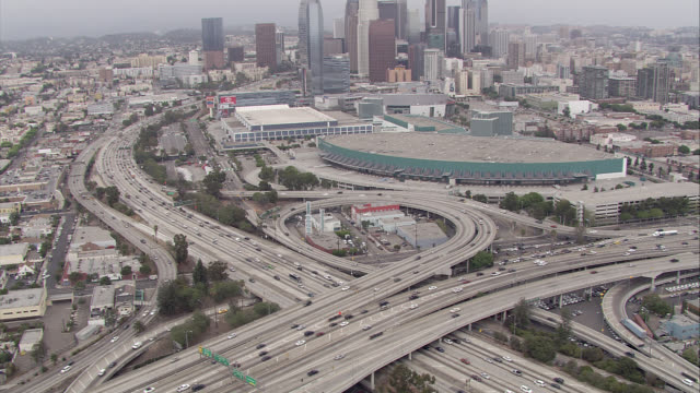 AERIAL OF DOWNTOWN LOS ANGELES SKYLINE, CONVENTION CENTER. HIGH RISES, SKYSCRAPERS, HOTELS, OFFICE BUILDINGS. PAN DOWN TO REVEAL HARBOR FREEWAY 110 AND HIGHWAY 101 INTERSECTIONS. BIRDSEYE POV OF CARS, TRAFFIC, OVERPASSES, RAMPS.