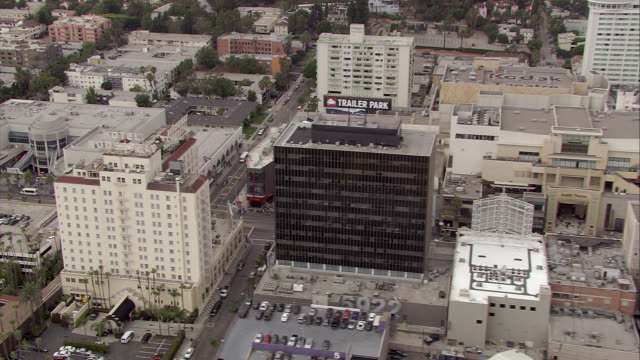aerial of hollywood area of los angeles. encircles roosevelt hotel and grauman's chinese theatre with hollywood walk of fame, crowds of people, tourists. birdseye pov. cars, tour buses, traffic, shops visible on hollywood blvd. city streets. hollywood and - mann theaters stock videos & royalty-free footage