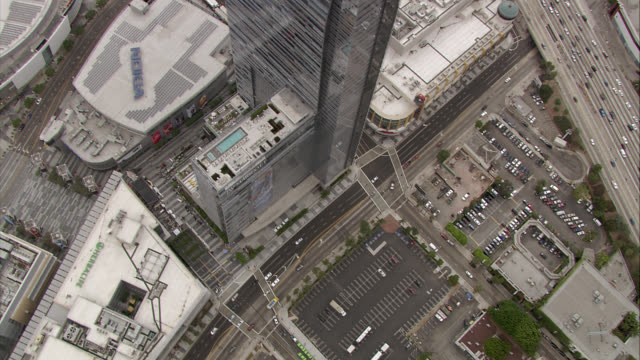 AERIAL BIRDSEYE POV OF STAPLES CENTER, DOWNTOWN LOS ANGELES. NOKIA THEATER, HIGH RISE GLASS BUILDING, RITZ CARLTON. OFFICE BUILDINGS. HIGHWAY WITH CARS AT RIGHT.