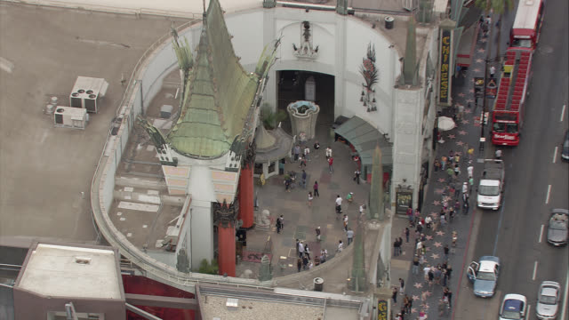 aerial of hollywood area of los angeles. encircles grauman's chinese theatre with hollywood walk of fame, crowds of people, tourists. birdseye pov. cars, tour buses, traffic, shops visible on hollywood blvd. city streets. hollywood and highland. tcl chine - the dolby theatre stock videos & royalty-free footage
