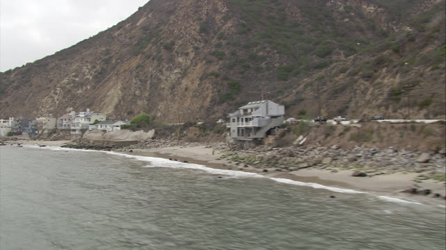 aerial of malibu beachfront houses along shoreline. waves from pacific ocean. sand, cliffs, hills, mountains. pacific coast highway with cars driving at right. residential areas, beach houses, vacation homes. rocks. - pazifikküste stock-videos und b-roll-filmmaterial