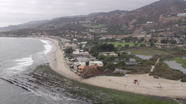 aerial of malibu beachfront houses along shoreline. waves from pacific ocean. sand, cliffs, hills, mountains. hotels, inns, or resorts. rental properties. residential areas, beach houses, vacation homes, beach towns. pacific coast highway with cars drivin - malibu stock videos & royalty-free footage