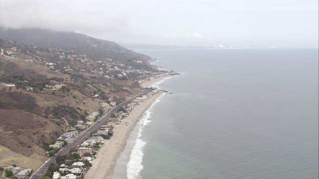 aerial of malibu beachfront houses along shoreline. waves from pacific ocean. sand, cliffs, hills, mountains. hotels, inns, or resorts. rental properties. residential areas, beach houses, vacation homes, beach towns. pacific coast highway with cars. boats - pazifikküste stock-videos und b-roll-filmmaterial