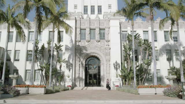 up angle of beverly hills city hall building. spanish renaissance architecture. pan down to entrance where woman carrying wheeled luggage exits building. zoom in, pull back toward entrance. pan up to building tower. palm trees at front entrance. governmen - back to front stock videos and b-roll footage