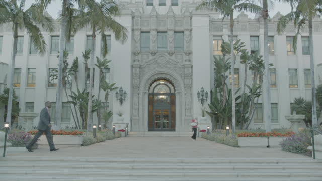 wide angle of beverly hills city hall building entrance. spanish renaissance architecture. woman exits building and businessman walks in fg from left to right. woman walks back into building entrance. palm trees at front entrance. government buildings. - back to front stock videos and b-roll footage