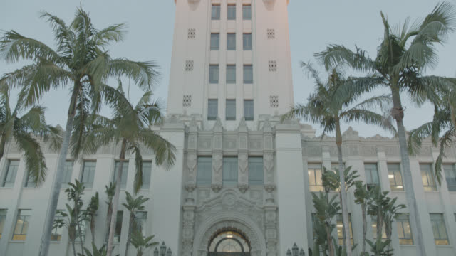up angle of beverly hills city hall building tower. pans down to front entrance and steps. spanish renaissance architecture. palm trees. government buildings. - government building stock videos & royalty-free footage