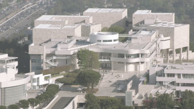 aerial of getty center in brentwood area of los angeles. hilltops, trees, cliffs. neighboring city skylines in far bg. landmarks. art museums. - brentwood los angeles stock videos & royalty-free footage