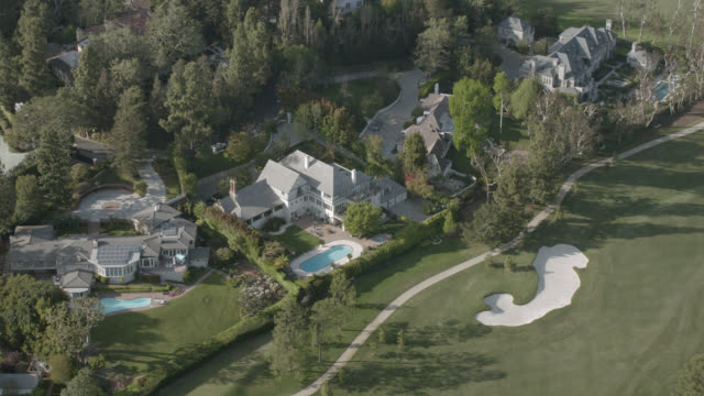 aerial of large estate mansions with swimming pools and neighboring golf course. could be in brentwood area of los angeles. trees, greens, fairways, sand traps, bunkers. upper class.. - brentwood los angeles stock videos & royalty-free footage
