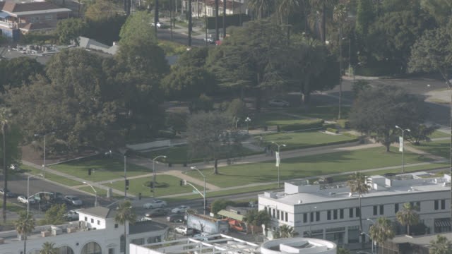 aerial of beverly gardens park in beverly hills. trees, grass, paths visible. entrance at santa monica blvd. and beverly dr. - santa monica blvd stock videos & royalty-free footage