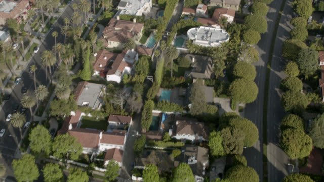 aerial birdseye pov of north beverly drive towards rodeo drive in beverly hills. rooftop upper class neighborhood houses, swimming pools, gardens. palm trees, shops, stores, office buildings, cars, traffic. upper class neighborhood. intersection at wilshi - beverly hills stock videos & royalty-free footage