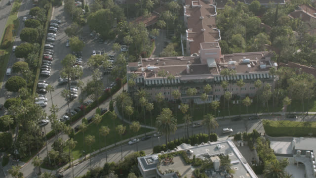 aerial of the beverly hills hotel. limousines parked in front, palm trees, swimming pools, tennis courts. birdseye pov of adjacent roads, intersection with traffic, cars. upper class neighborhood. - beverly hills stock videos & royalty-free footage