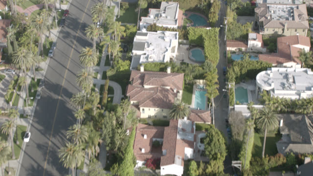 stockvideo's en b-roll-footage met aerial birdseye pov of north beverly drive towards rodeo drive in beverly hills. rooftop upper class neighborhood houses, swimming pools, gardens. palm trees, shops, stores, office buildings, cars, traffic. upper class neighborhood. intersection at wilshi - beverly hills californië