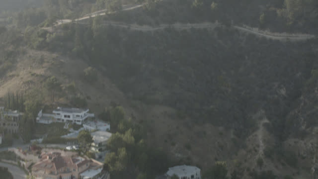 aerial of large multi-story hillside houses near griffith observatory in los angeles. middle upper class. roads, trees, mount lee and the hollywood sign visible in bg. - griffith observatory stock videos & royalty-free footage