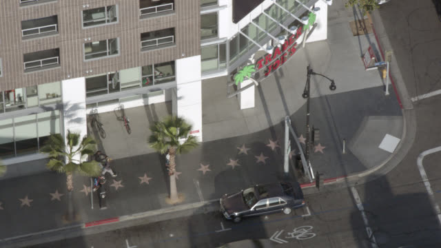 aerial birdseye pov of hollywood walk of fame, corner vine and selma streets. famous sidewalk with stars on pavement. cars, traffic, pedestrians, high rises. could be condominium or apartment building. billboards, palm trees. - walk of fame bildbanksvideor och videomaterial från bakom kulisserna