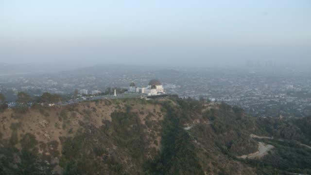 aerial of griffith observatory with trees, cliffs, hilltops, mountains. domed buildings. sun halations. almost sunset. - griffith observatory stock videos & royalty-free footage