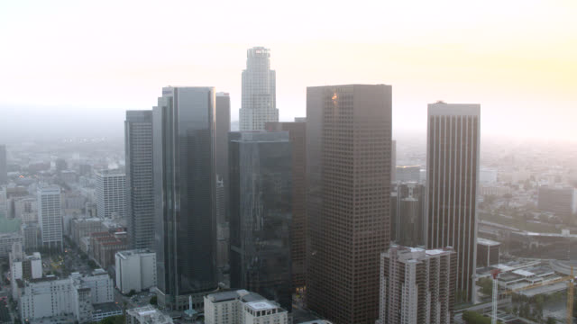 aerial of los angeles skyline at sunset. downtown core with bank of america, aon, and u.s. bank tower, buildings. skyscrapers, high rises. cranes, apartment and office buildings visible. - us bank tower stock videos & royalty-free footage