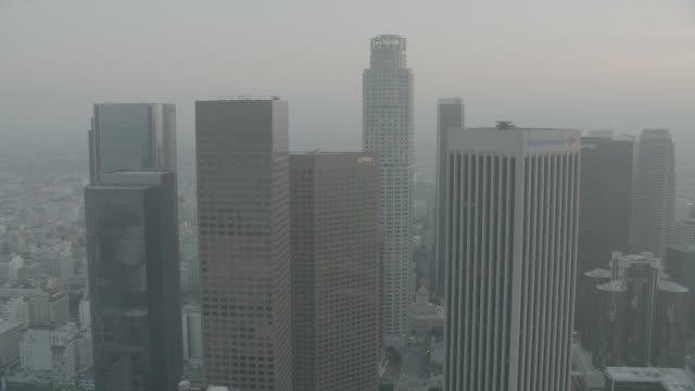 AERIAL OF LOS ANGELES SKYLINE AT SUNSET. DOWNTOWN CORE WITH BANK OF AMERICA, KPMG, WELLS FARGO, DELOITE AND TOUCHE, 777 TOWER, GAS COMPANY TOWER, AON, 611 PLACE, TWO CALIFORNIA PLAZA, AND U.S. BANK TOWER, BUILDINGS. SKYSCRAPERS, HIGH RISES. CRANES, APARTM