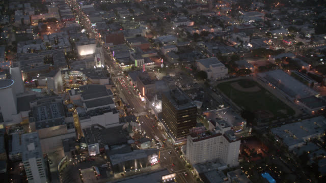 vídeos de stock e filmes b-roll de aerial of city streets and building rooftops in hollywood area near hollywood and highland. loews hollywood and roosevelt hotel, dolby theatre, high rises, office buildings, hollywood and highland center, city lights, cars, traffic. - the dolby theatre