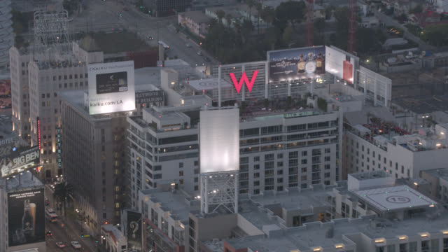 vidéos et rushes de aerial of vine street hotels in hollywood, california at dusk. w hotel, the broadway hollywood, the knickerbocker hotels, capitol records building. billboards, city lights, apartment and office buildings. city streets with cars, traffic. landmarks. - hollywood boulevard