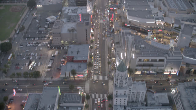 aerial of hollywood blvd. birdseye pov of roosevelt hotel. dolby theatre, formerly kodak theatre,  hollywood and highland, high rises, apartment or office buildings. city lights. traffic with cars visible. - the dolby theatre stock videos & royalty-free footage