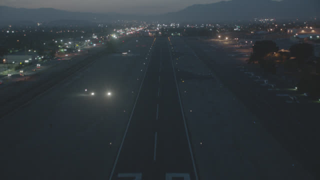 vidéos et rushes de aerial of small landing strip or pad at dusk. small air traffic control tower, blinking lights. mountains in far bg. - tour de contrôle