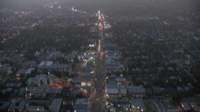 vídeos de stock e filmes b-roll de aerial of sunset boulevard from sunset and labrea toward west hollywood. city streets and building rooftops. building rooftops, strip malls. city lights, cars, traffic. birdseye pov of streets and pans up toward hollywood hills and hillside houses and apa - west hollywood