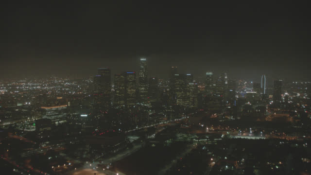 AERIAL OF LOS ANGELES SKYLINE AT NIGHT. DOWNTOWN CORE WITH BANK OF AMERICA, KPMG, WELLS FARGO, DELOITE AND TOUCHE, 777 TOWER, GAS COMPANY TOWER, AON, 611 PLACE, TWO CALIFORNIA PLAZA, AND U.S. BANK TOWER, BUILDINGS. SKYSCRAPERS, HIGH RISES. APARTMENT AND O
