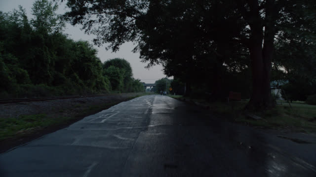 process plate straight back of country road in rural area. road wet. farms and fields with horses visible on right. railroad track on left. trees visible. - country road stock videos & royalty-free footage