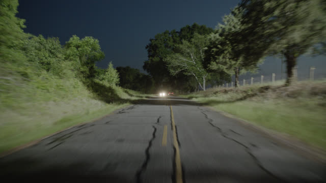 process plate straight back of country road in rural area with trees or woods. farms and fields with horses visible on right. railroad track on left. car passes through illuminated section of forest. cars on road swerve to avoid camera. could be car chase - country road stock videos & royalty-free footage